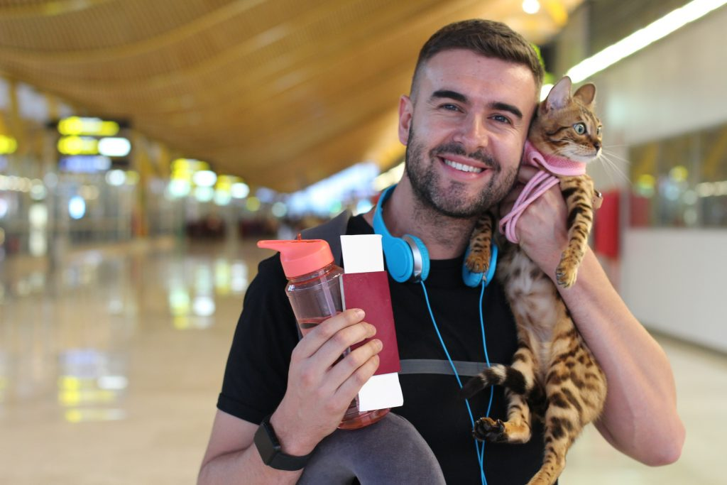 man holding pet cat and other items, smiling at airport.