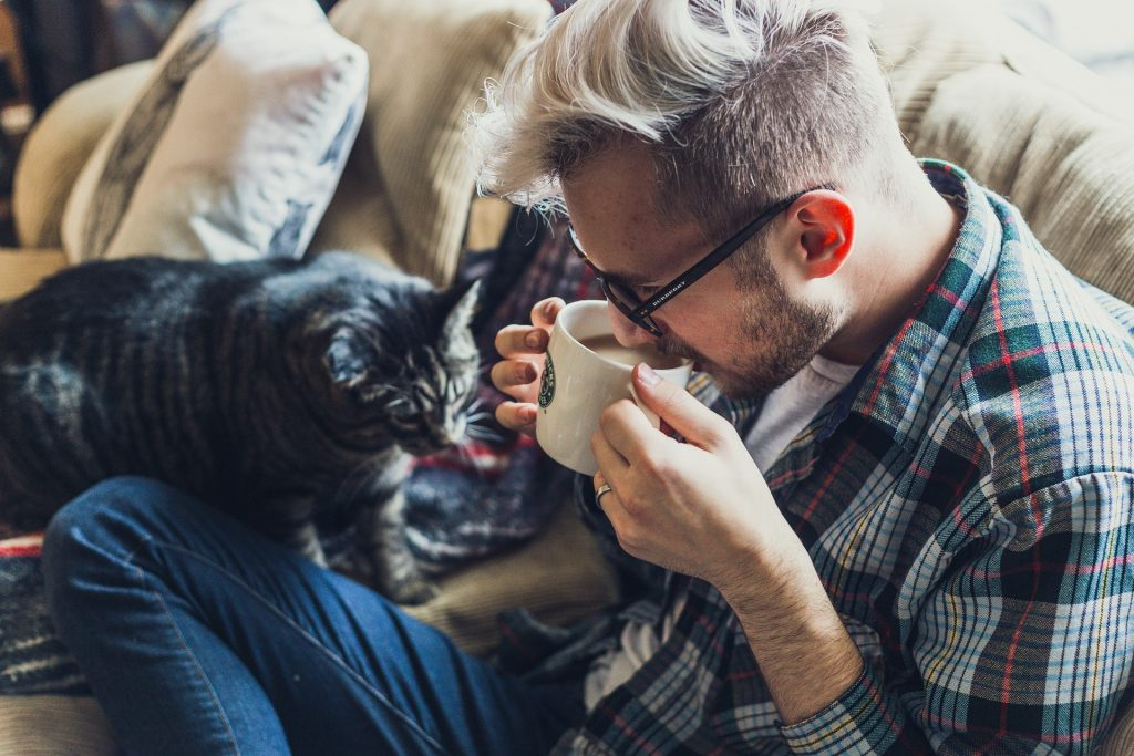 man drinking coffee while sitting on a couch with a cat.